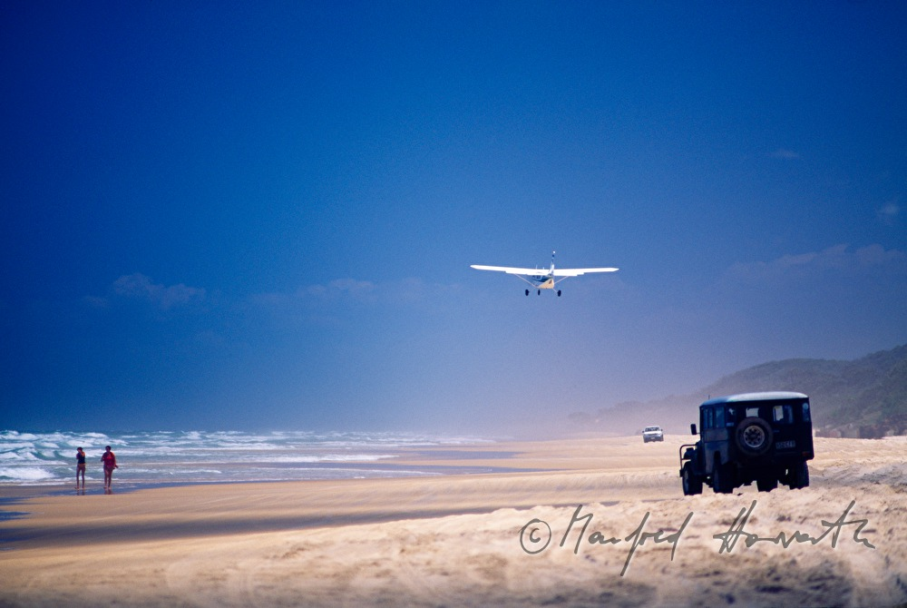 a plane lands on the beach
