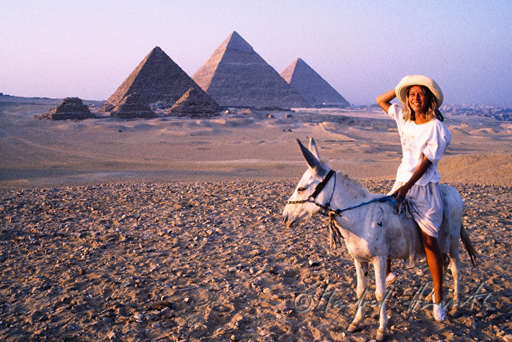 Giza Necropolis and tourist riding a donkey