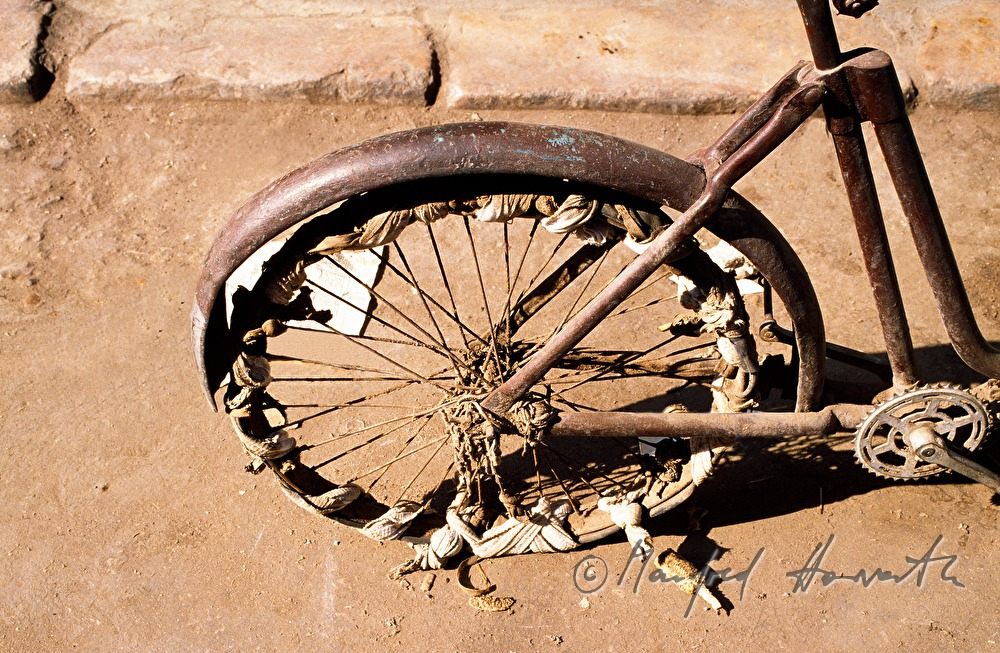 very old bicycle with patched wheel